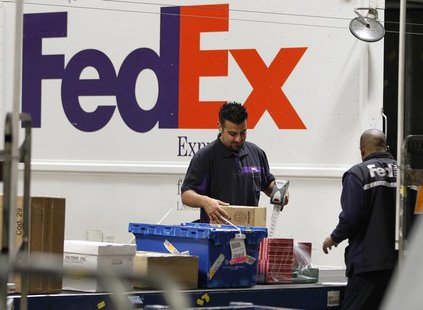 Handlers scan and affix a courier route label onto packages moving down the belt at the Marina Del Rey, California FedEx station December 12