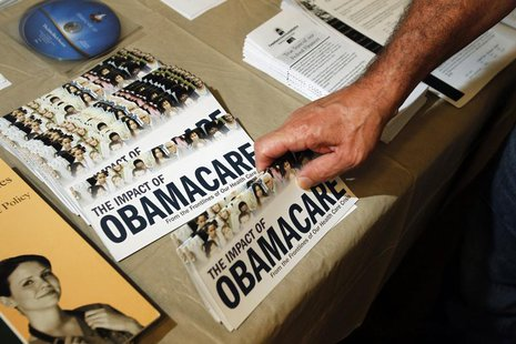 "A Tea Party member reaches for a pamphlet titled ""The Impact of Obamacare"" in Littleton, New Hampshire October 27, 2012. REUTERS/Jessica Rin"