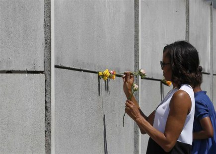 U.S. first lady Michelle Obama (L) and her daughter Sasha place flowers as they visit the Berlin Wall memorial in Bernauer Strasse in Berlin