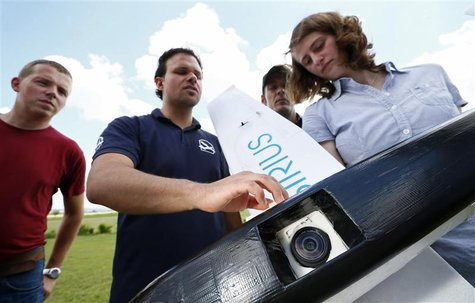 "Michael Niesen (2nd L) of MAVinci explains the camera equipped ""Sirius"" unmanned aerial vehicle (UAV) during a training session for clients"
