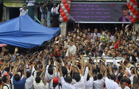 Myanmar pro-democracy leader Aung San Suu Kyi waves to supporters as she leaves the National League for Democracy party headquarters after a