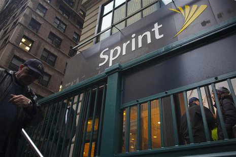 Pedestrians walk past a Sprint store in New York in this December 17, 2012 file photo. REUTERS/Andrew Kelly/Files