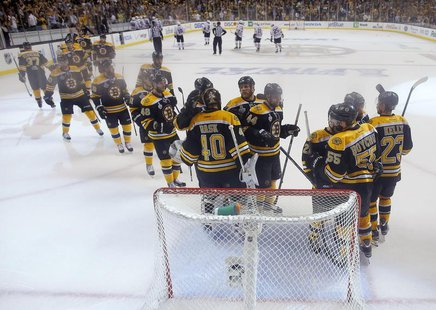 Boston Bruins goalie Tuukka Rask (40) is congratulated by hs teammates after shutting-out the Chicago Blackhawks in Game 3 of their NHL Stan