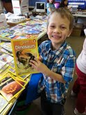 Noah Thurman, first grade, excited about a non-fiction dinosaur book