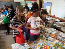 Fourth graders:  Angelina Hinz, Chardonnay Traylor, Peter Vang, Aliziah Blevons (in the background holding the green bag) selecting their new books.