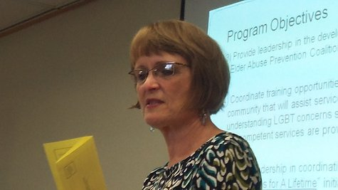 Judy Sivak, Director of the Area Agency on Aging with a copy of the flyer in her hand.