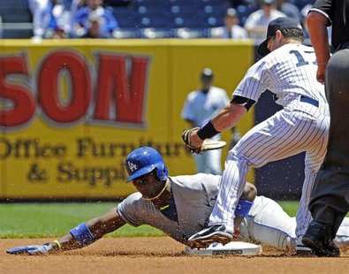 Los Angeles Dodgers' Yasiel Puig is tagged out by New York Yankees shortstop Jayson Nix (R) as Puig attempts to stretch a single into a doub