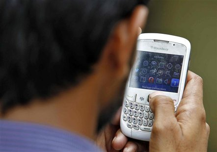 A man checks his mobile phone near a marketplace in New Delhi June 18, 2013. REUTERS/Anindito Mukherjee