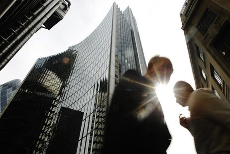 Pedestrians pass office blocks in the City of London June 19, 2013. REUTERS/Luke MacGregor