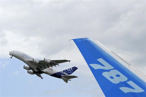 The vertical stabilizer of a Boeing 787 Dreamliner is seen as an Airbus A380, the world's largest jetliner, takes off during the 49th Paris
