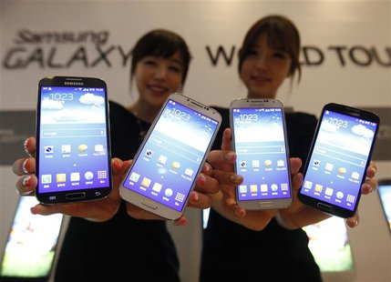 Models pose for photographers with Samsung Electronics Co Ltd's latest flagship smartphone S4 during its launch event at the company's headq