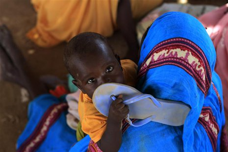 A child holds a slipper as displaced people wait at a food distribution centre as special envoys and diplomats arrive for a meeting to discu