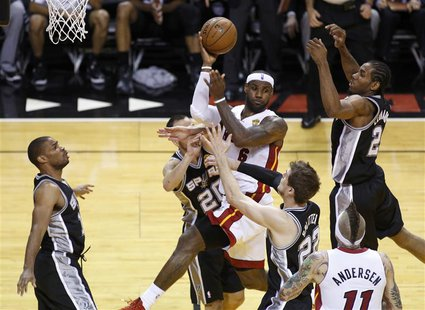 Miami Heat's LeBron James (6) is surrounded by San Antonio Spurs' Gary Neal (L), Manu Ginobili (20), Kawhi Leonard (2) and Tiago Splitter (2