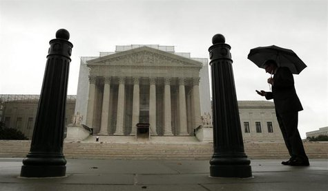 A man holds an umbrella outside the U.S. Supreme Court in Washington June 10, 2013. REUTERS/Kevin Lamarque