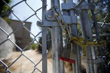 A lock secures a chain on the steel fence of a foreclosed home previously owned by U.S. Bancorp in Los Angeles, California July 17, 2012. RE