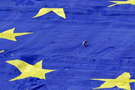 An organiser walks on a large European Union flag displayed in front of Romania's Parliament Building to mark EU Day in Bucharest May 9, 201