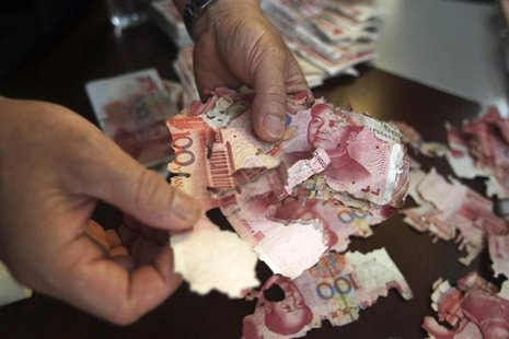 Damaged 100 yuan banknotes are seen at a branch of China Bank in Foshan, Guangdong province, June 5, 2013. REUTERS/Stringer