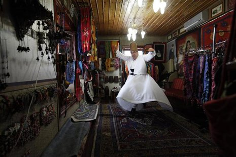 Turkish felt artist and a whirling dervish Celalettin Berberoglu performs a Sama practice in his shop in the central Anatolian city of Konya