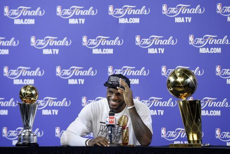 Miami Heat's LeBron James sits with the Larry O'Brien Trophy and the Bill Russell MVP Trophy after his team defeated the San Antonio Spurs i
