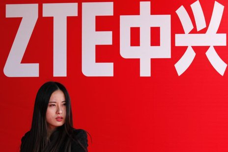 A woman stands in front of a ZTE company logo during the company's 15th anniversary celebration in Beijing April 18, 2013. REUTERS/Barry Hua