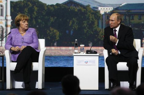 Russia's President Vladimir Putin (R) and Germany's Chancellor Angela Merkel attend a session of the St. Petersburg International Economic F