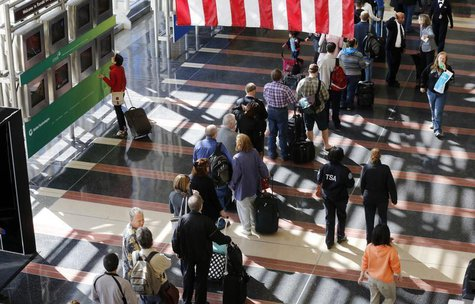 A line of passengers wait to enter the security checkpoint before boarding their aircraft at Reagan National Airport in Washington, April 25