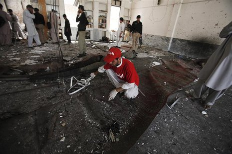 A rescue worker collects evidence from the site of a suicide bomb attack at a Shi'ite Muslim mosque in Peshawar June 21, 2013. REUTERS/Fayaz