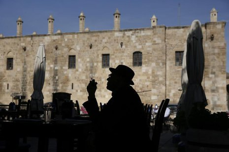 A man smoking a cigarette is silhouetted in front of Buyuk Han (The Great Inn) in Nicosia, Northern Cyprus March 25, 2013. REUTERS/Yorgos Ka