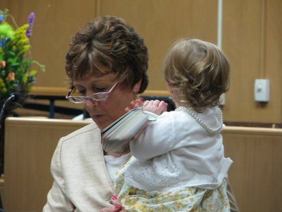 Wife and Wausau City Attorney Anne Jacobson speaks during her husband's ceremony, with help from their granddaughter.