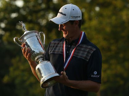 England's Justin Rose looks at the U.S. Open Trophy after winning the 2013 U.S. Open golf championship at the Merion Golf Club in Ardmore, P