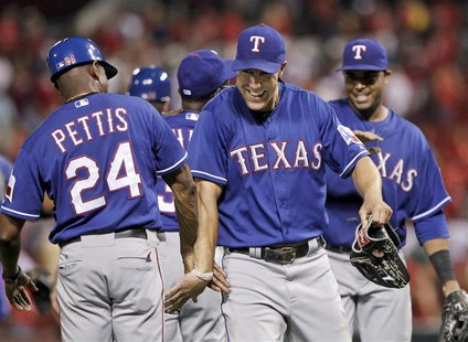 Texas Rangers left fielder David Murphy celebrates with third base coach Gary Pettis (L) after beating the St. Louis Cardinals 6-4 in their