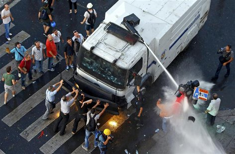 Protesters try to stop an armored crowd control truck from which the riot police fire water cannon at Taksim Square in Istanbul June 22, 201