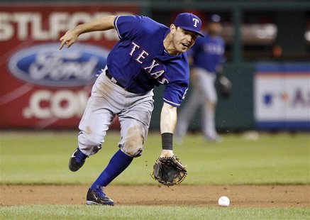 Texas Rangers second baseman Ian Kinsler fields a ball hit by St. Louis Cardinals second baseman Matt Carpenter during the eighth inning of