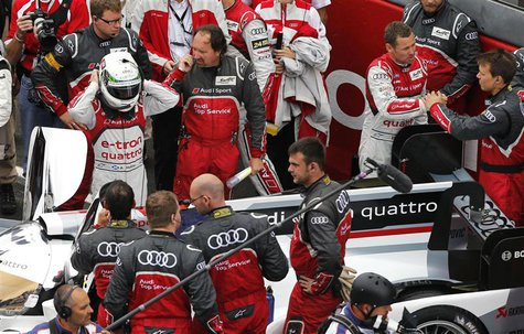 Driver of Audi R18 E-Tron Quattro Allan McNish (L) of Britain adjusts his helmet as driver number 2 Tom Kristensen (R) of Denmark speaks wit