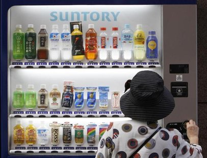 A woman purchases a Suntory beverage from a vending machine in Tokyo September 10, 2009. REUTERS/Yuriko Nakao