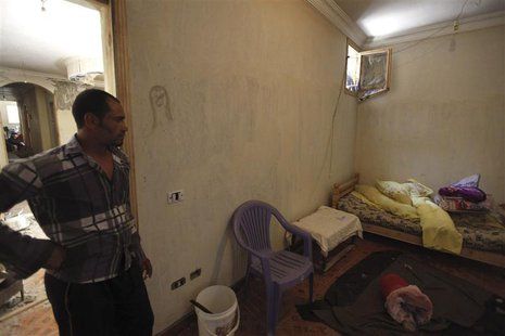 A man enters the room of a house, where four Egyptian Shi'ites were killed, in the suburb of Zawiyat Abu Musallem, on the outskirts of Cairo
