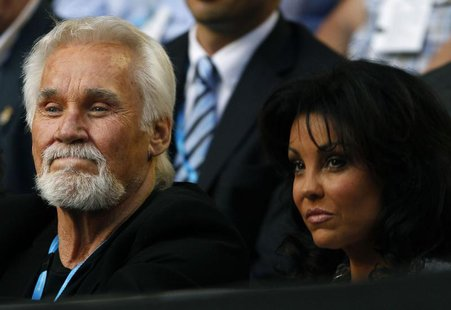 Singer Kenny Rogers and his wife Wanda Miller watch the match between Rafael Nadal of Spain and Marin Cilic of Croatia at the Australian Ope