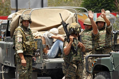 Lebanese army soldiers gesture as they capture a gunmen in Sidon, southern Lebanon, June 24, 2013. REUTERS/Ali Hashisho