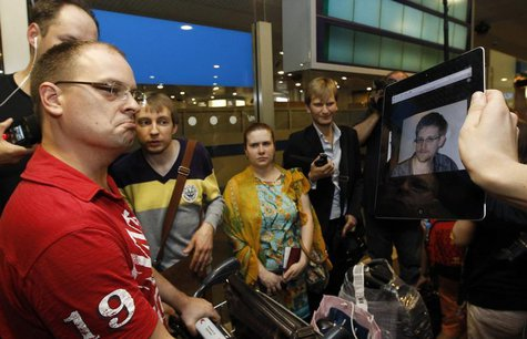 Journalists show an iPad with the picture of Edward Snowden, former contractor for the U.S. National Security Agency, to passengers of a fli
