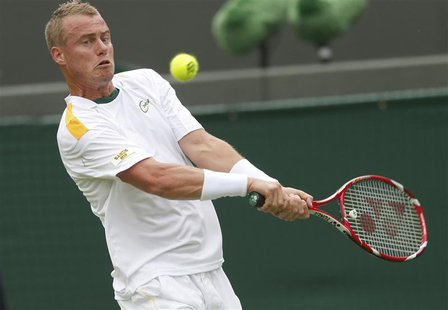 Lleyton Hewitt of Australia hits a return to Stanislas Wawrinka of Switzerland during their men's singles tennis match at the Wimbledon Tenn