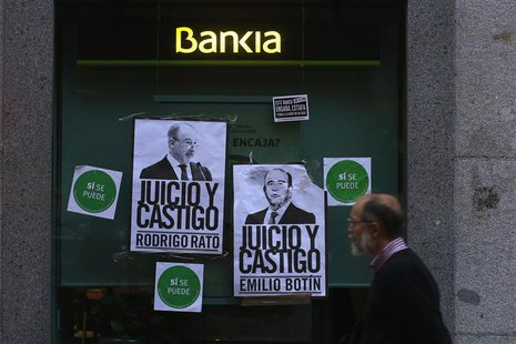 A man walks past a branch of Spain's lender bank Bankia with two posters depicting former Bankia CEO Rodrigo Rato (L ) and Emilio Botin, cha