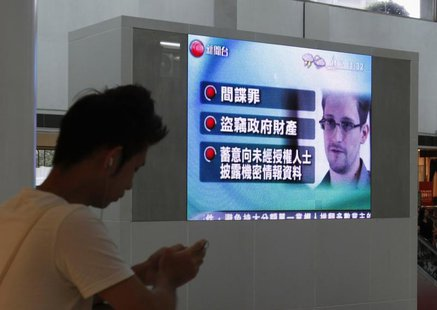 A man checks his mobile phone in front of a monitor broadcasting news on U.S. charges against Edward Snowden, a former contractor at the Nat