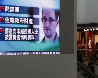 A monitor broadcasts news on the charges against Edward Snowden, a former contractor at the National Security Agency (NSA), by the United St