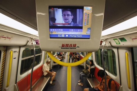 Edward Snowden, a former contractor at the National Security Agency (NSA), is seen during a news broadcast on a screen inside a train in Hon