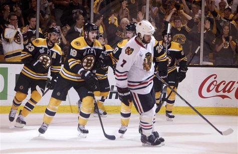 Boston Bruins Chris Kelly (23) skates off with teammates Tyler Seguin (19) and Daniel Paille (20) behind Chicago Blackhawks Brent Seabrook (