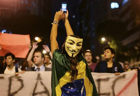 A demonstrator wearing a Guy Fawkes mask takes photos on her mobile phone during a protest in central Rio de Janeiro June 24, 2013. REUTERS/