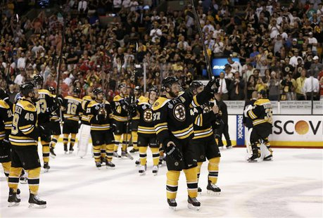 Boston Bruins' Patrice Bergeron (C) leads his team in saluting the crowd after losing to the Chicago Blackhawks in Game 6 of their NHL Stanl