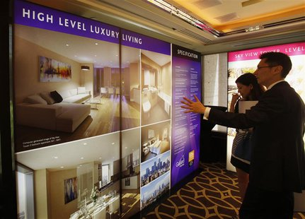 A sales representative (R) speaks to a visitor in front of photographs of a London upmarket property development for sale, inside a luxury h