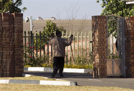 A village elder greets security personnel as he enters the home of former South African President Nelson Mandela, in Qunu June 25, 2013. REU