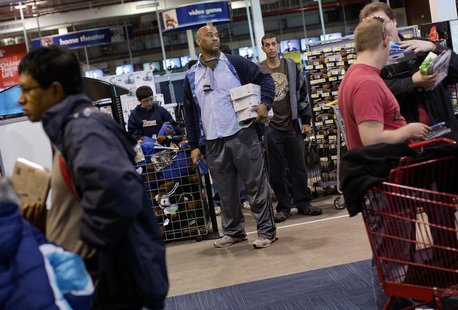 A man waits in line to purchase items at the Best Buy electronics store in Westbury, New York November 23, 2012. REUTERS/Shannon Stapleton